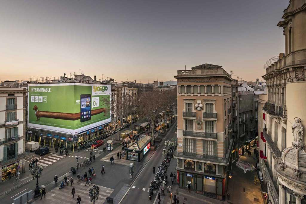 Publicidad Exterior: Lona Publicitaria en Barcelona para YOIGO, ubicada en la fachada de un céntrico edificio de la Ramblas